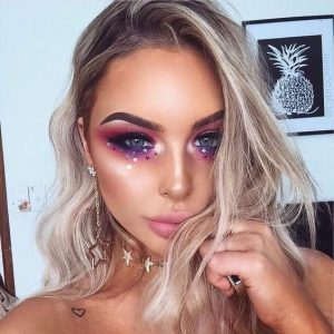 blonde with heavy eye makeup festival style